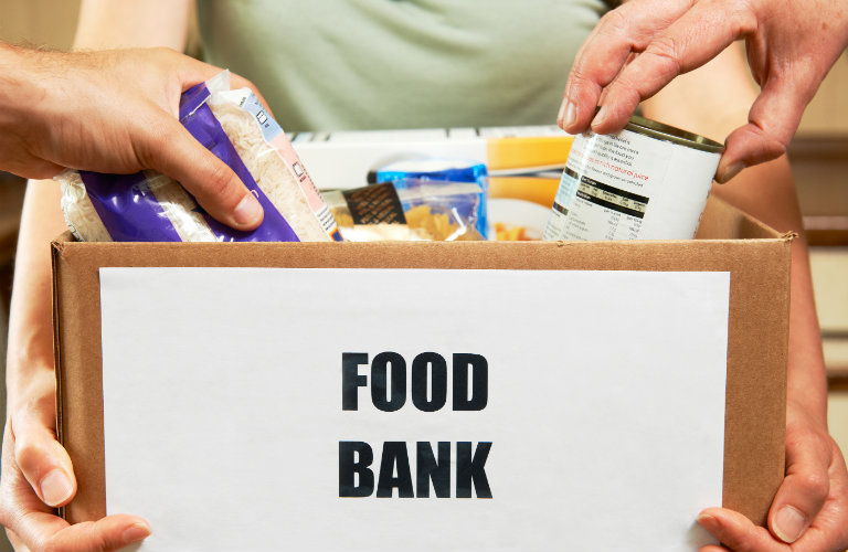 People-putting-food-into-box-for-food-bank