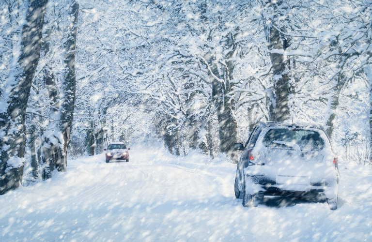 Two-cars-driving-down-snow-covered-road