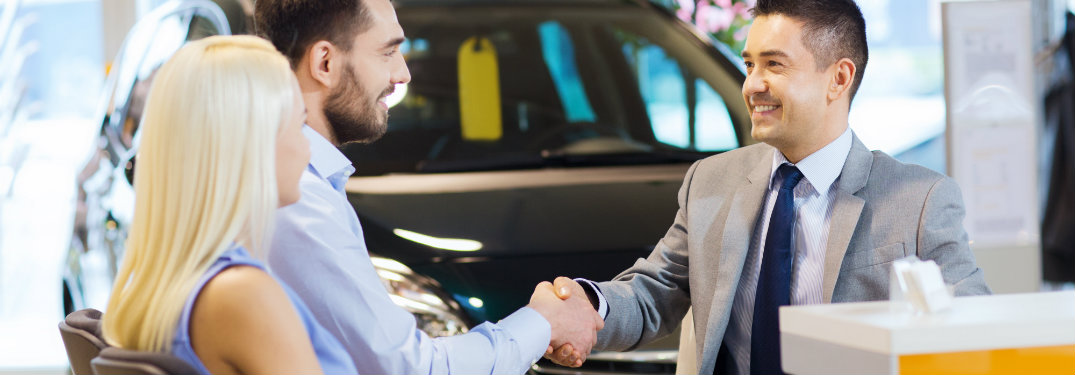 Young-couple-shaking-hands-with-salesman-at-car-dealership