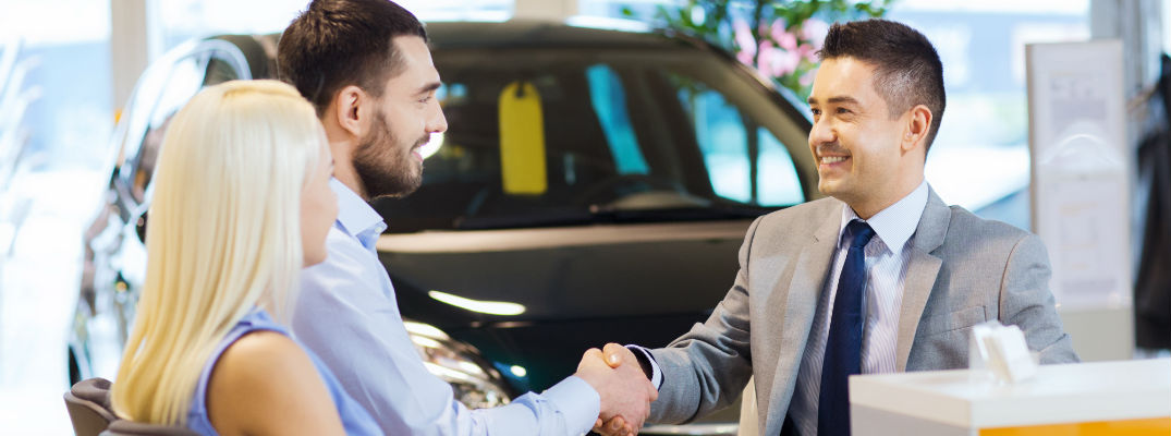 A stock photo of a young couple completing a transaction with a dealership's representative