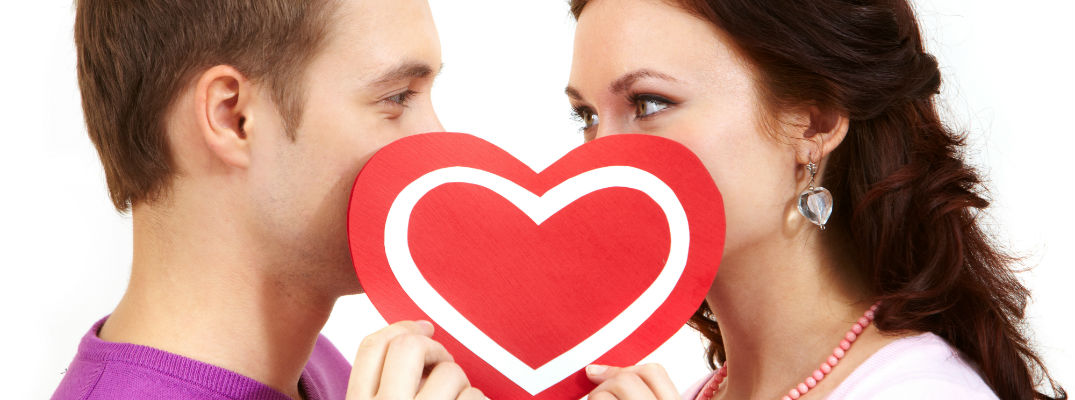 A stock photo of a young couple's faces hidden behind a paper heart