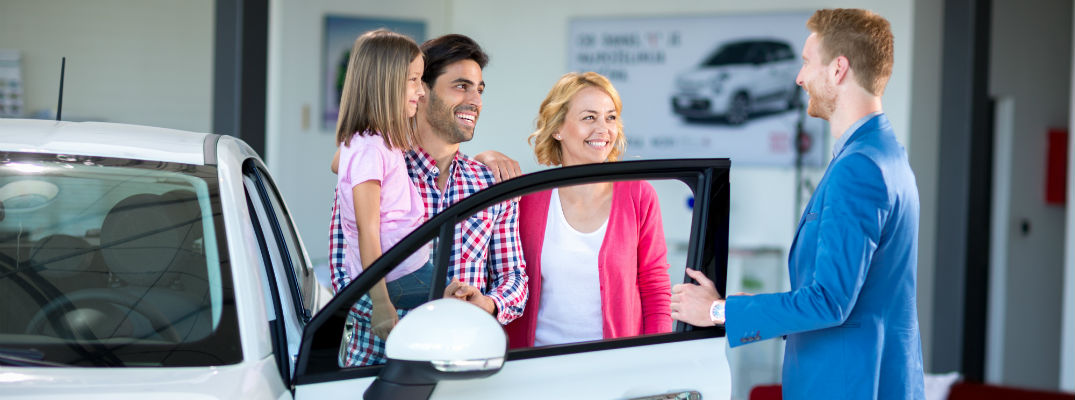 A stock photo of a young family learning more about the new vehicle they're buying