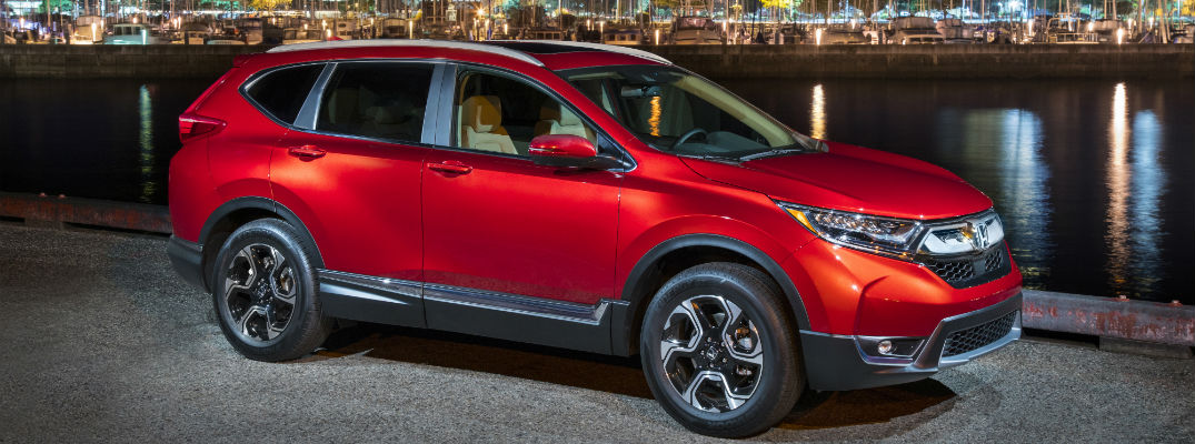 A right profile photo of a 2018 Honda CR-V in front of a harbor