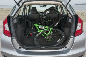 2018 Honda Fit exterior back fascia open trunk with green bike inside on beach