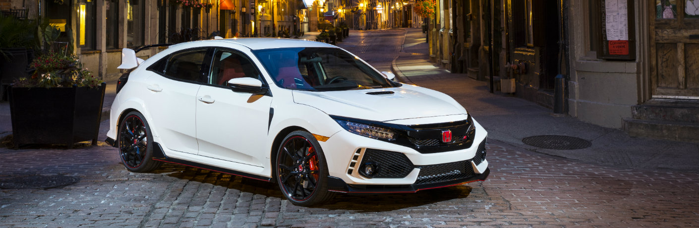 2017 and 2018 Honda Civic Type R white paint coat parked in the tiled street of a european old-fashioned village