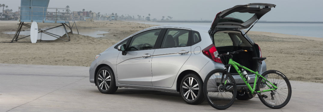2018 Honda Fit with open trunk and green bike on beach