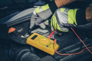 changing car battery with yellow gloves on