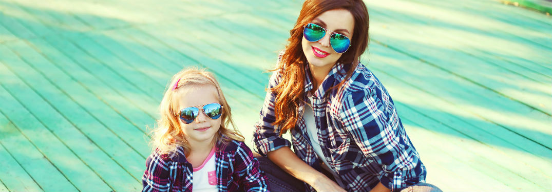 Mother and daughter in matching flannel outfits and sunglasses sitting on blue deck