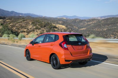 orange-2019-Honda-Fit-driving-on-rural-road-with-mountains-in-background