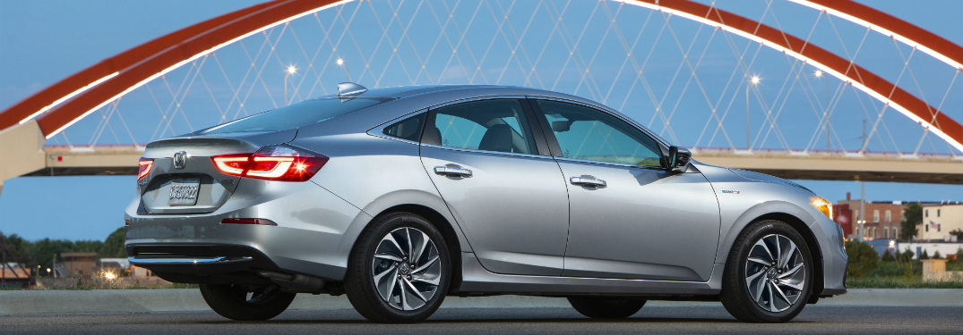2019 Honda Insight driving past a bridge