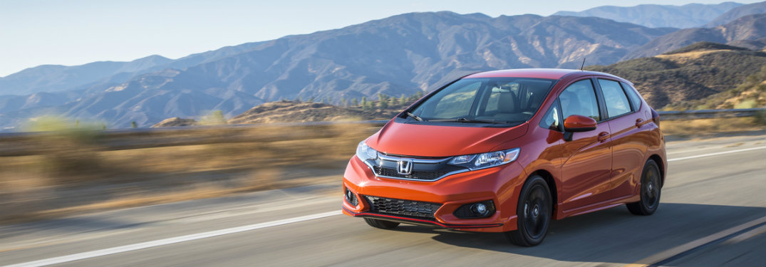 orange honda fit driving by mountains