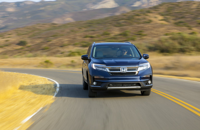 front view of blue honda pilot on rural road