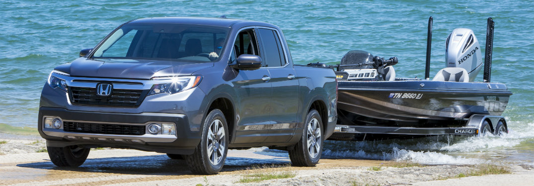gray honda ridgeline pulling boat out of water