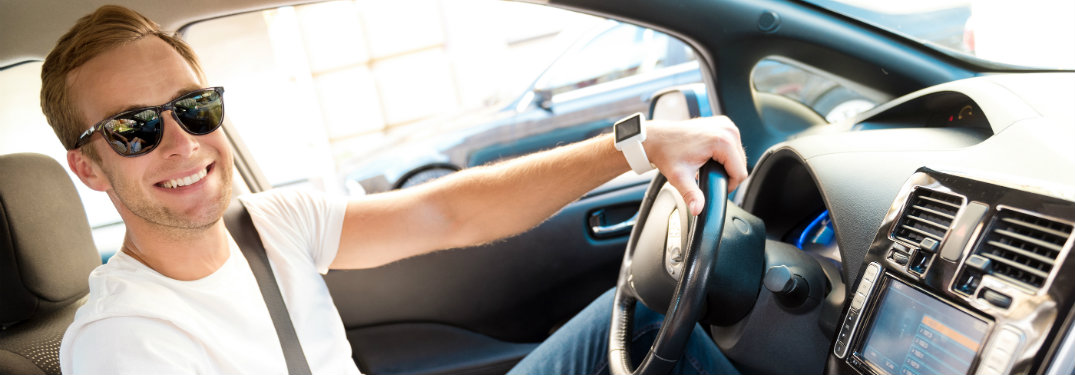 man smiling holding steering wheel
