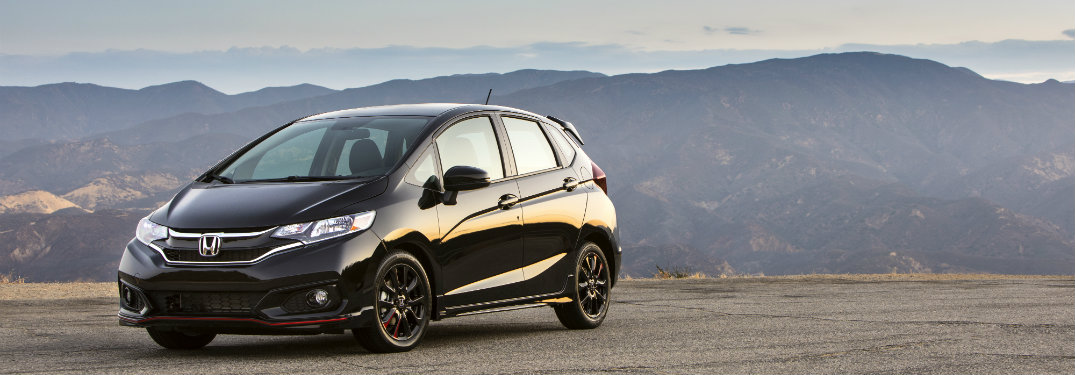 left side view of black honda fit with mountains in background