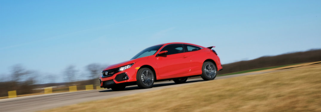 left side view of red honda civic si driving