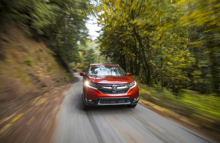 front view of red honda cr-v driving by trees