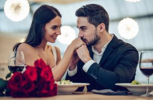 man kissing woman's hand at dinner table