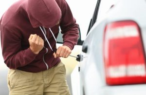 man with hoodie trying to break into car