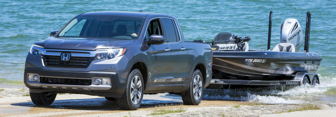 Front driver side exterior view of a gray 2019 Honda Ridgeline pulling a boat out of the lake