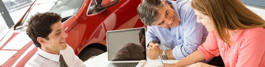 Happy family signing paperwork for their new fuel-efficient car purchase at a dealership