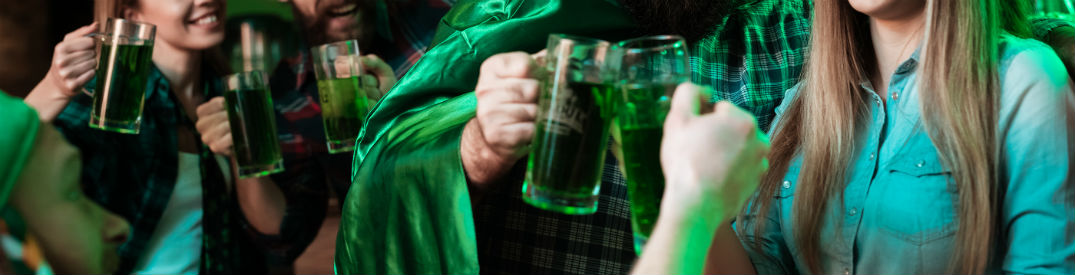 People toasting with mugs full of green beer