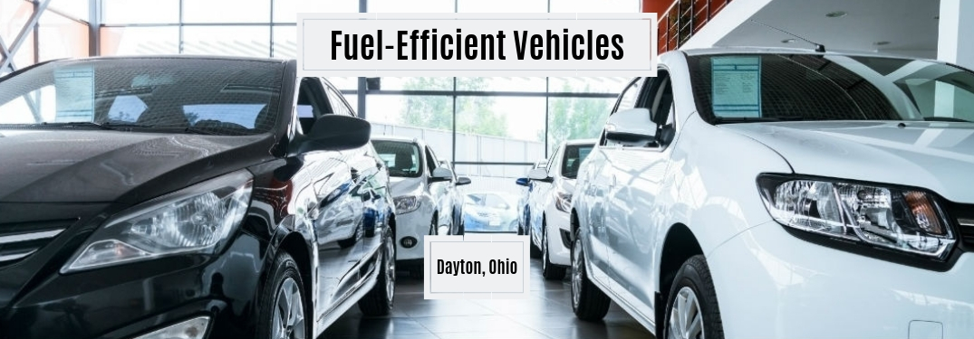 Fuel-Efficient Vehicles Dayton, OH., text on an image of a black sedan on the left parked next to white sedan on the right in a car dealer's showroom