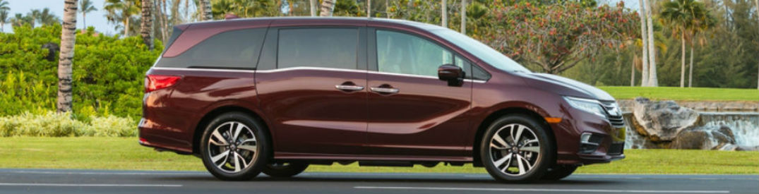 Passenger side exterior view of a red 2019 Honda Odyssey