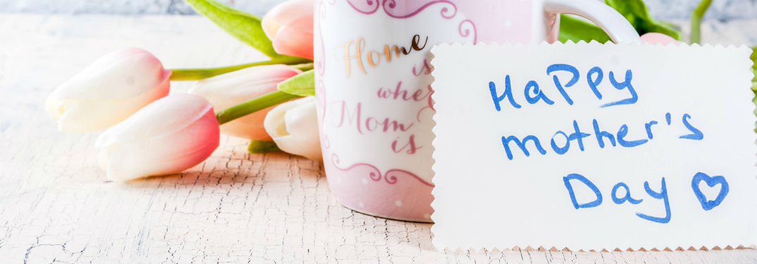 """Happy Mother's Day"" written on a place card at a table set in front of a coffee mug and pink roses"