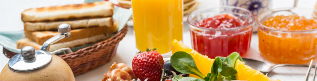 A plate of fruit in front of jam, orange juice, and a basket of toast at a Mother's Day brunch