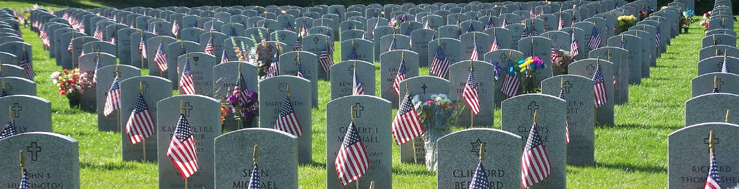Headstones adorned with American flags for Memorial Day