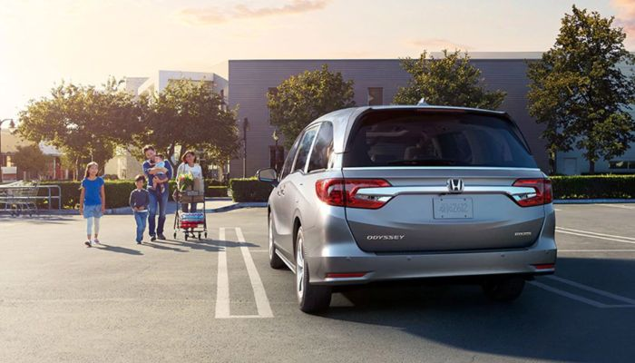 A family walking towards a parked 2020 Honda Odyssey in a parking lot