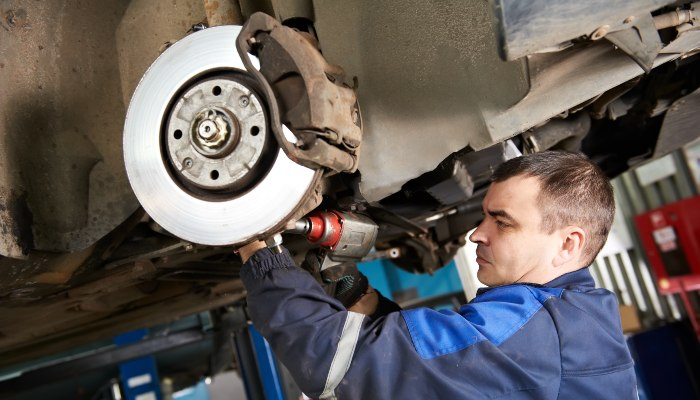 A mechanic working on a car's brakes