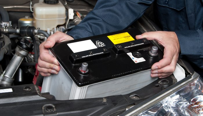 A car mechanic replaces a battery in a car.