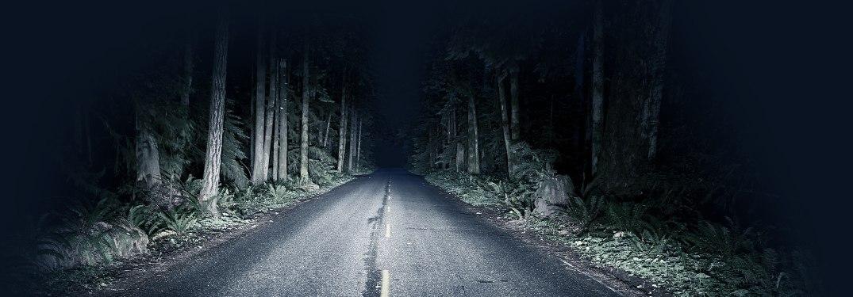 A dark road illuminated by headlights