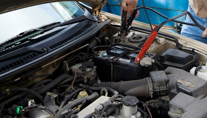 A mechanic using jumper cables on a car battery