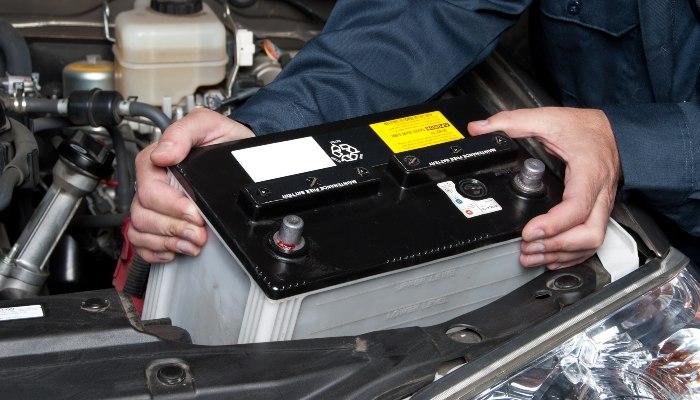 A mechanic replacing a car battery