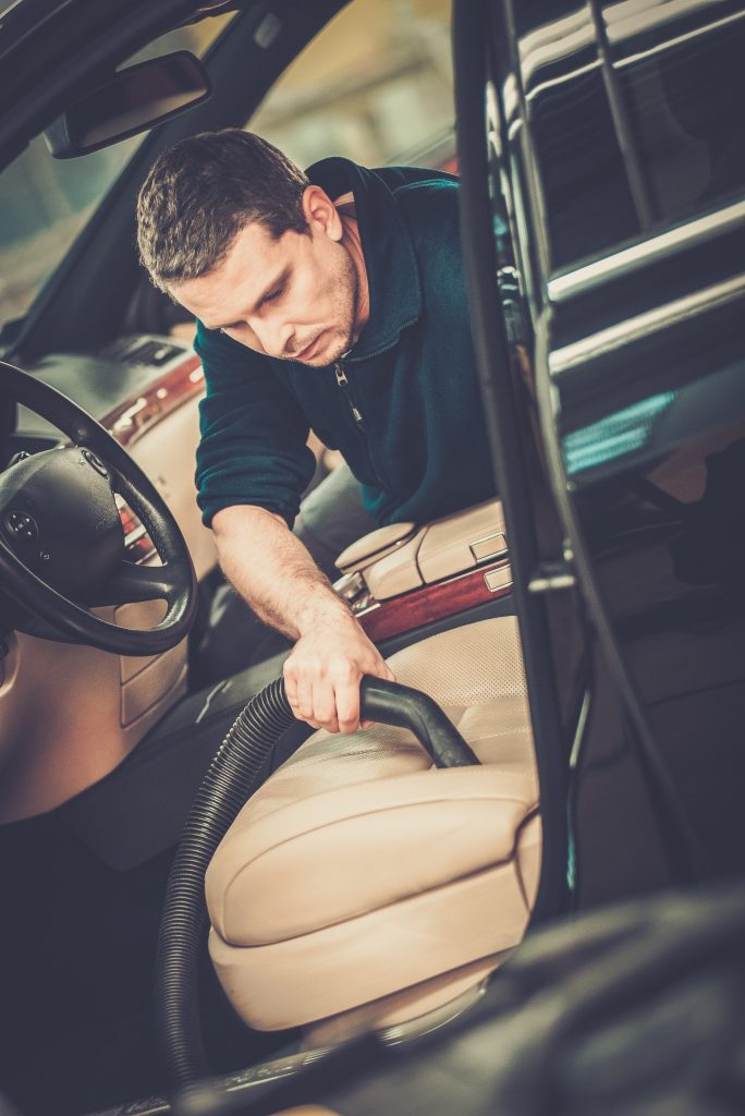 A man vacuuming a vehicle interior