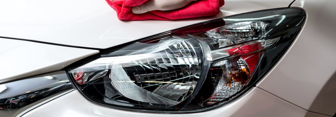 A person cleaning a vehicle's headlights with a red cloth