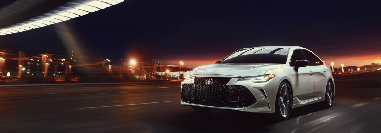 2019 Toyota Avalon Hybrid driving through a city at night