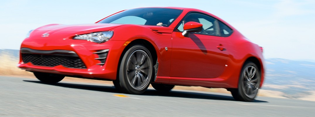 Red 2019 Toyota 86 driving on hilly country road