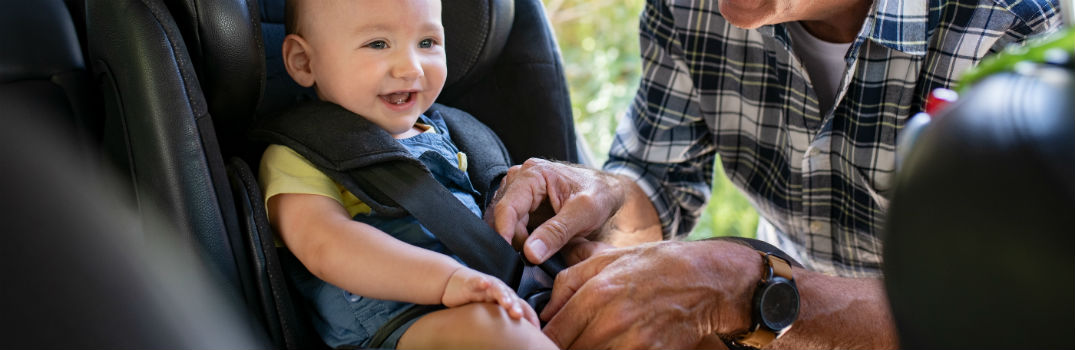 Grandfather Strapping Child into Car Seat