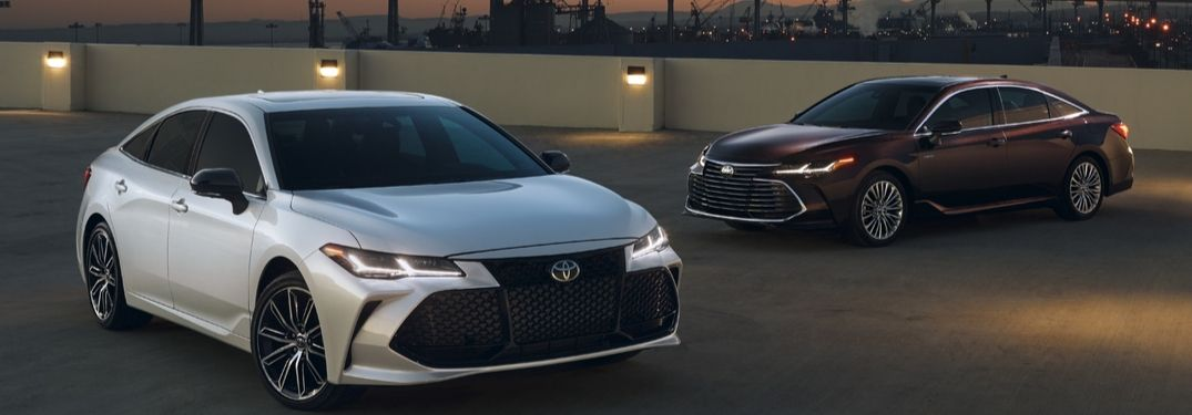 2020 Toyota Avalon Touring on left and Hybrid Limited on right with city in background