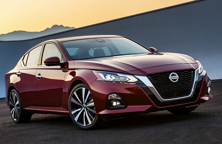 Exterior Image Of A Maroon 2019 Nissan Altima Parked Outside At Dusk With  Mountains In The
