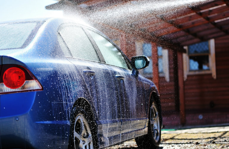 blue car being sprayed with water