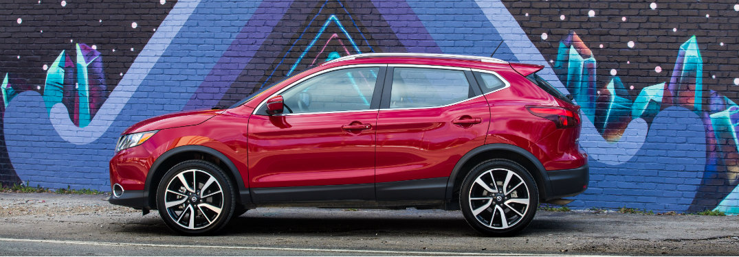 left side of red nissan rogue parked by colorful cement wall