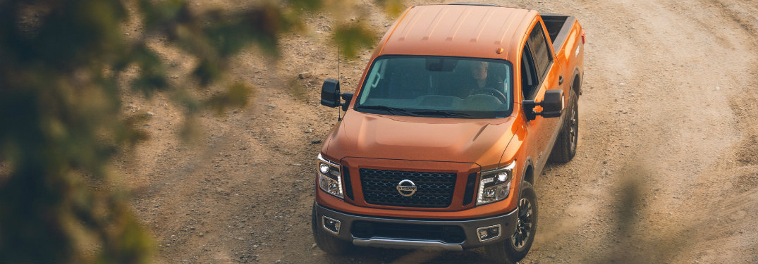 aerial view of orange nissan titan on dirt path