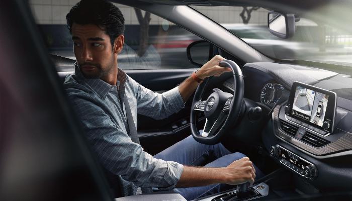 A man driving a 2020 Nissan Altima