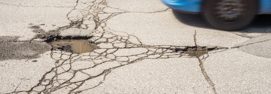 A car approaching a pothole