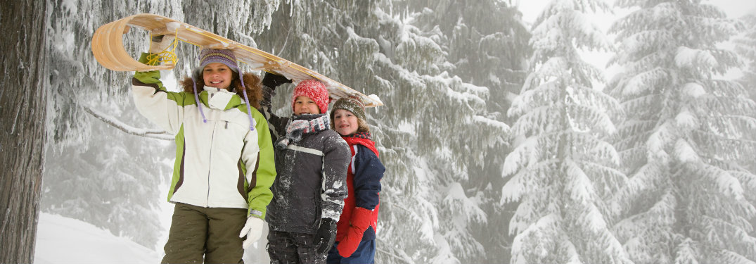 Kids-holding-sled-in-front-of-snow-covered-trees
